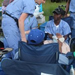 An NP assesses her patient's foot while a BSN provides foot care.