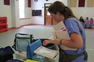 Becca Owings checks to make sure her case load of kids has visited each of the screening stations.