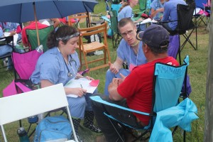 Pharmacy students help farmworkers get the right medications at night camp.