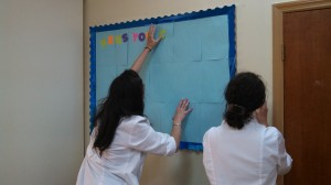 Annie and Kelly work on a bulletin board- just one of our many educational projects for this trip.