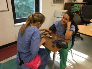 Alejandra and Grace practice taking manual blood pressures