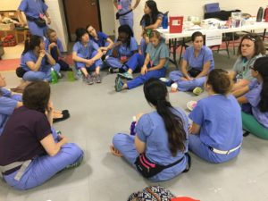 Nursing students start their day by discussing the events of night camp